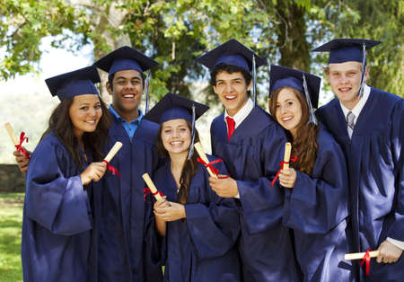 Graduating students smiling and laughing with diplomas; trees in background