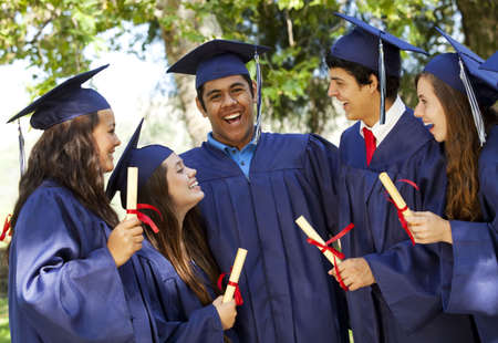 Graduating students smiling and laughing with diplomas; trees in background photo