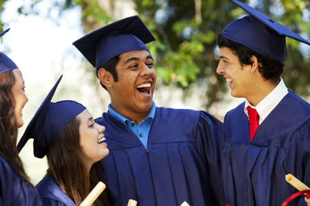 Graduating students smiling and laughing with diplomas; trees in background Stock Photo - 7734261