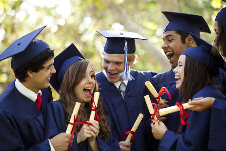 high school: Graduating students smiling and laughing with diplomas; trees in background