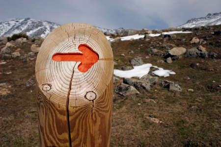 Wooden sign with orange arrow on snowy mountain with blue sky