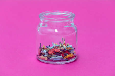 isolated people inside a glass jar on a pink background