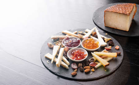 Cheese board with nuts and marmalades on a black slate background - gastronomy - gourmet