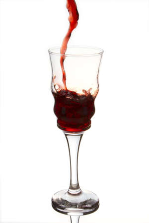 Crystal glass that slowly fills with a refreshing and red wine  Stock Photo