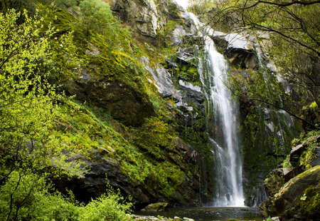 beautiful waterfall in the middle of a mountain with lots of vegetation