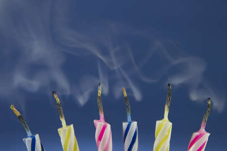 Detail of colorful birthday candles recently blown where you see the smoke.
