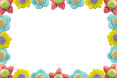 Frame made of jelly bean flowers of different colors and with lots of sugar on a white background.
