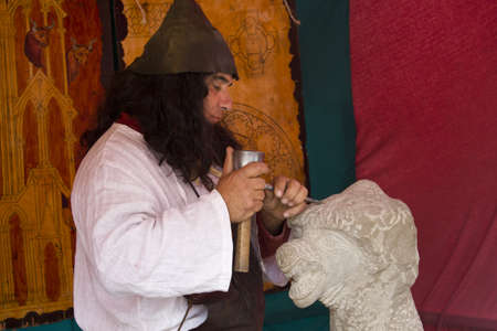 Sculptor carving a stone figure in the Medieval fair on June 9, 2012 in the town of Lalin, Spain.