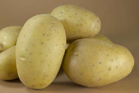 Group of potatoes on a brown background. Stock Photo