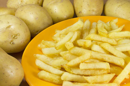 royalty free stock photos: Plate of chips surrounded by a group of potatoes even without cooking.