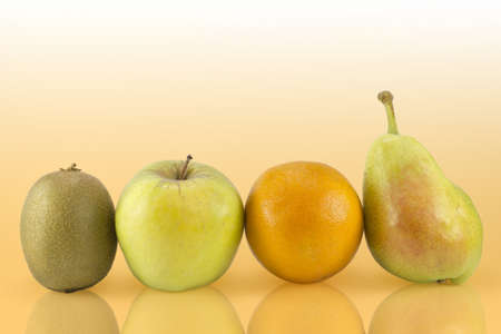 Group of various fruits like kiwi, apple, orange and pear on an orange background.