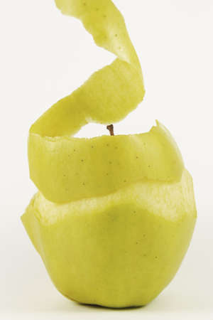 A yellow apple peeling to eat, on a white background.