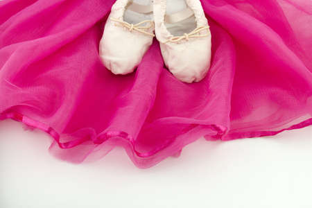 Photography of a ballet shoes of a girl on her pink ballet skirt. Stock Photo