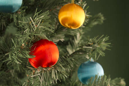 Several colored spheres hanging from a green Christmas tree.
