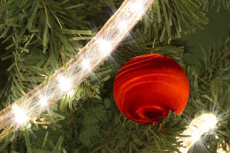 Christmas red ball on the tree decorated with lights. Stock Photo