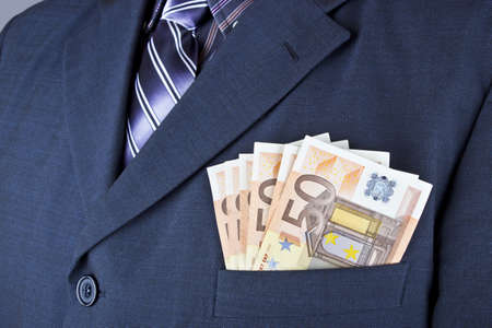 Close up to euro banknotes coming out of the jacket pocket of a man  photo