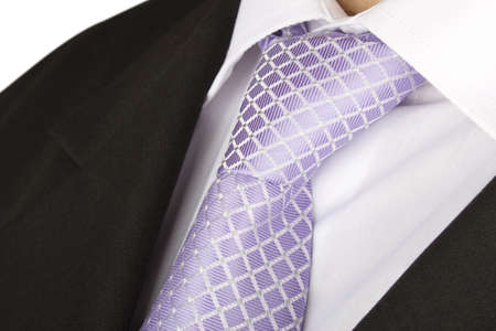 Close up of a purple tie over a white shirt and a black suit
