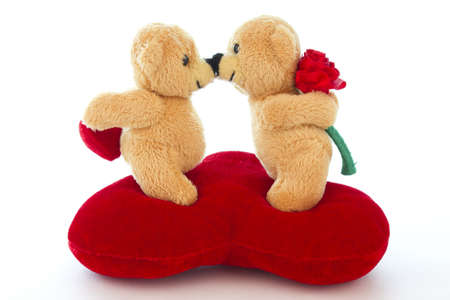 Teddies kissing on a red heart on a white background.