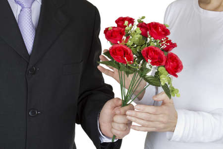 A man gives a bouquet of plastic roses to a woman on a white background.