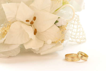 Bouquet of white flowers with wedding rings on a white background. Stock Photo