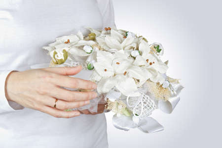 Woman holding a bridal bouquet of white flowers on a gray background. Stock Photo