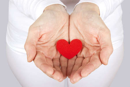 Women caring for a fabric heart with both hands on a gray background.