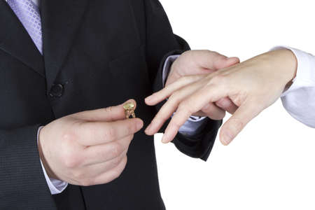 A man gives engagement ring to his girlfriend on a white background.