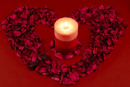 Red candle within a heart of rose petals on a red background. Stock Photo