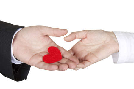 A man shares a fabric heart with a woman on a white background. Stock Photo
