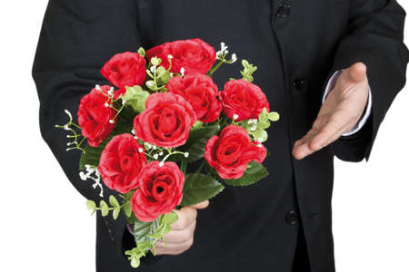 A man gives a bouquet of plastic roses to the camera on a white background.