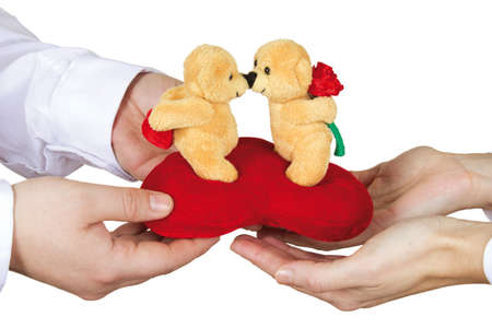 A man gives a woman a teddy bear as a gift on a white background.