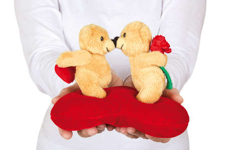A woman gives a teddy bears in love to the camera on a white background. photo