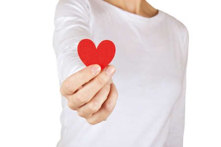 Woman gives a fabric heart to the camera on a white background. Stock Photo