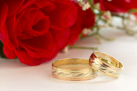 Close up to the wedding rings with bouquet of red roses on a white background.