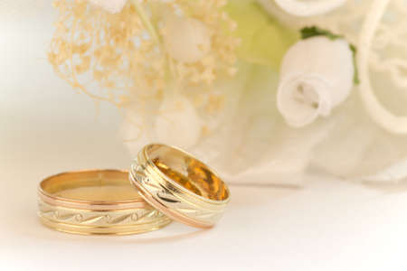 Close up to the wedding rings with bouquet of white flowers on a white background.