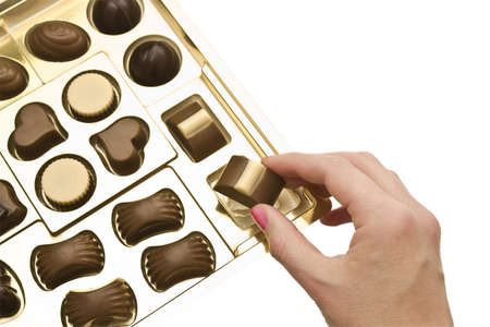 Hand of a woman holding a chocolate from a box of chocolates