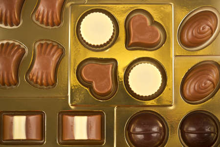 Golden box with chocolates of different shapes, colors and flavors