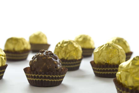 hazelnut chocolate balls wrapped in gold paper on a white background Stock Photo