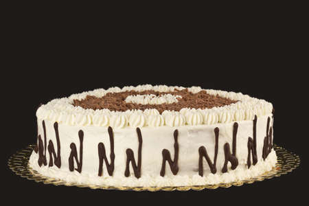 Photograph of a cake with cream and chocolate on a brown background.