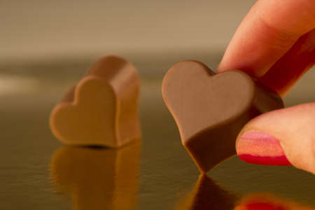 Hand of a woman holding a heart shaped chocolate Stock Photo