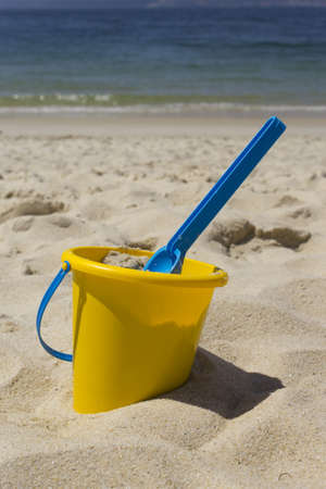 Picture of a bucket with his shovel in the sand at the beach. Stock Photo