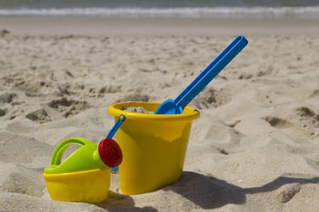 Picture of a bucket with his shovel and a watering can in the sand at the beach.