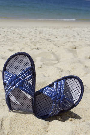 Picture of flip flops on beach sand in a hot summer day.