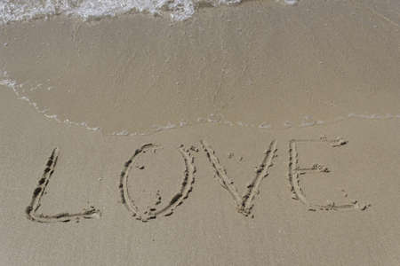 Photograph of the word love written in the sand on the beach and that is being cleared with the waves.