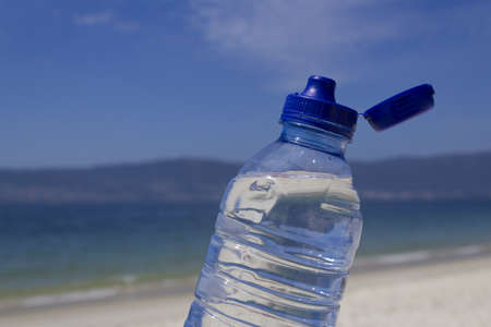 Photo of a water bottle on a sunny day at the beach.