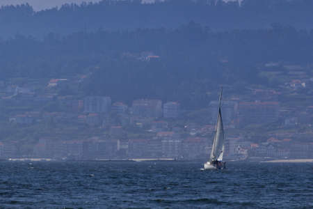 Picture of a sailboat crossing the sea to the coastal town in Pontevedra, Spain.