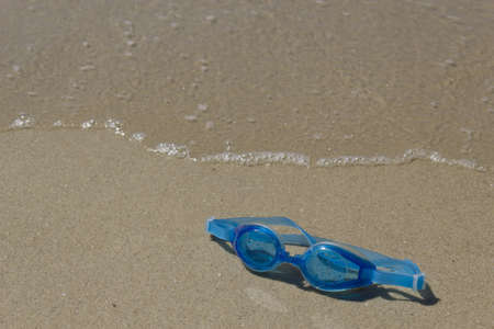 Picture of swimming goggles on the beach sand in sunny day.  Stock Photo