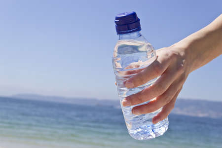 Picture of womans hand holding a water bottle on a hot day at the beach. photo