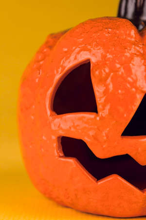 Close up of a halloween pumpkin on a yellow background. Stock Photo