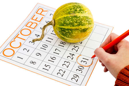 A womans hand pointing to the Halloween day, on a calendar along with a small pumpkin.